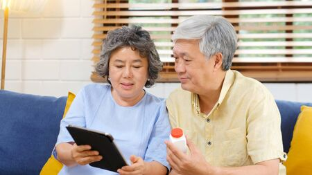 Photo pour Senior asian couple holding bottle of pill using digital tablet to make video conference call to doctor, pharmacy consulting about medical health care for retirement, old people, elderly and technology - image libre de droit