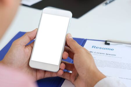 Photo pour Man hand holding smartphone with blank on screen device over resume application for job recruitment, job search , business concept - image libre de droit