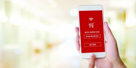 Photo pour E-coupon, Shopping online, Hand using mobile phone with discount coupon on screen, online shopping sale on smartphone, digital marketing, retail business and technology, e commerce promotion concept - image libre de droit