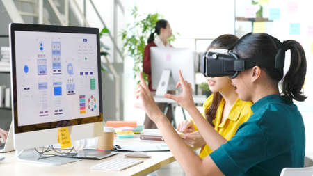 Foto de VR mobile phone application test, Asian woman with virtual reality glasses headset in VR experience, Asia business team developers for reality simulator smartphone app test at creative office, ui - Imagen libre de derechos