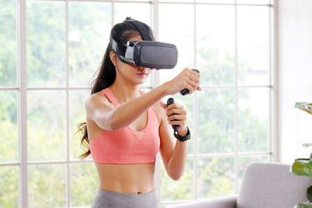 Photo for E sport, Happy asian woman wearing virtual reality headset for interactive excercise at home, Asia girl playing vr while workout fitness, Female and wearable technology - Royalty Free Image