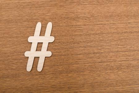 Foto de Hashtag sign made of wooden material on wooden background. Top view - Imagen libre de derechos