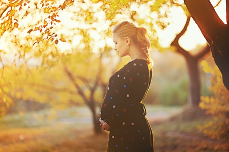 beautiful pregnant young woman outside, warm sunny pictureの写真素材