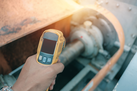 Foto de Hand holding of infrared thermometer inspection temperature machinery for preventive maintenance in factory - Imagen libre de derechos