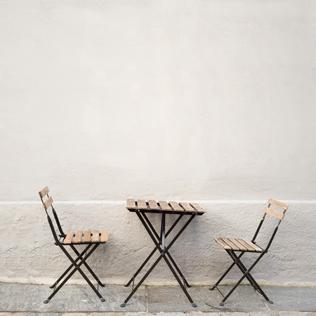 Photo for outdoor table and two chairs near the wall at coffee shop, Bergen, Norway - Royalty Free Image