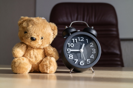 Alarm clocks and teddy bears placed on the a desk with sunshine in the afternoon / concept father and son.