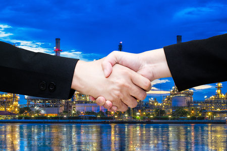 Close-up of business people handshaking in Oil refinery at twilight background /teamwork