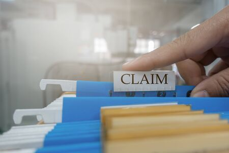 Foto de Human hand is picking up the claim document in the file for the client to the insurance company.insurance concept. - Imagen libre de derechos