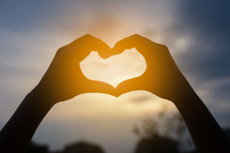 Photo for human hands in heart shape framing in sunset - Royalty Free Image