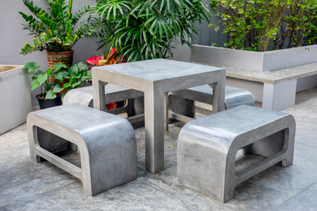 Photo pour Concrete outdoor furniture set in the small garden including on table and four benches - image libre de droit