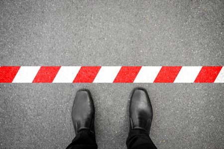 Photo for black shoes standing at the red-white line. Do not cross the line. It's prohibited and not allowed. It's limited. It's the end. - Royalty Free Image