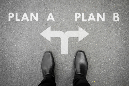 Businessman in black shoes standing at the crossroad making decision which way to go - plan A or plan B for his business