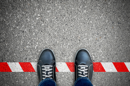 Photo pour Black shoes standing on the red-white line. Breaking the rule. It's prohibited and not allowed. It's limited. It's the end. - image libre de droit