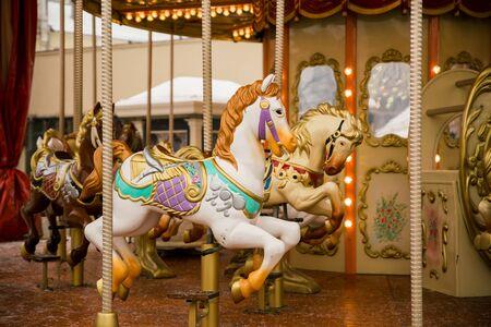 Photo pour merry go round carousel with white horse closeup, winter - image libre de droit