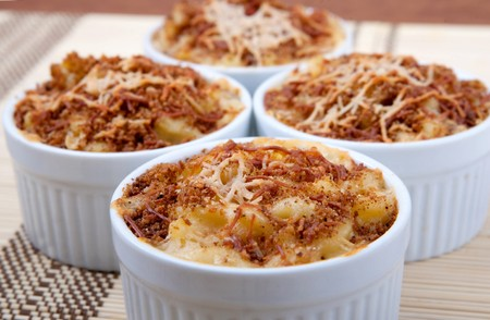 four ramekin bowls of homemade macaroni and cheese dinner topped with brown toasted cheesy crust