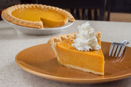 Foto de one slice of pumpkin  pie removed from the whole and ready to eat - Imagen libre de derechos