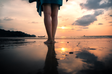 legs of young woman from behind standing on beach in front of golden sunset during holiday