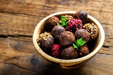 Photo pour Various Homemade Raw Vegan Truffles or Energy Balls, such as Almond and Cacao, Dark Chocolate and Hazelnut Butter inside wooden Plate and Rustic Background - image libre de droit