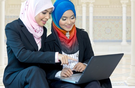 Young Asian muslim girls discuss with laptop
