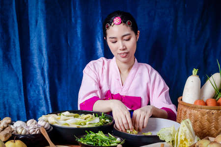 Foto de Korean women wearing traditional pink hanboks doing kimchi She is mixing the ingredients in the bowl. To taste delicious. The concept of charming fermented cooking And fragrant, Asian food - Imagen libre de derechos
