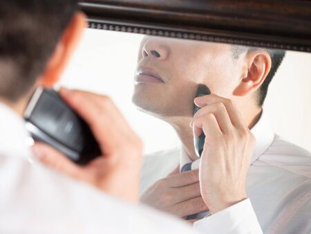 a male businessman who shaves in a hurry while looking in the mirror