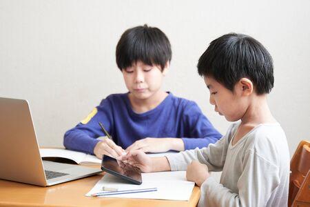 Photo pour Japanese elementary school students studying online at home - image libre de droit