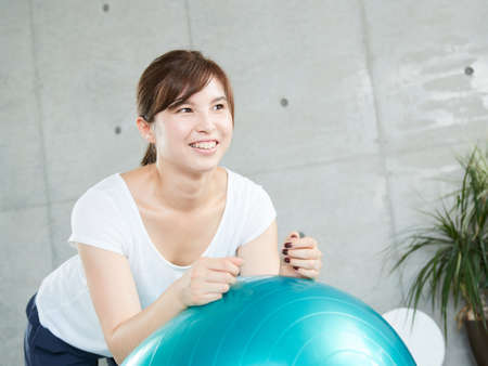 Japanese woman using balance ball to plank