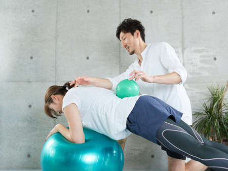 Japanese woman being taught by Planck by a personal trainer