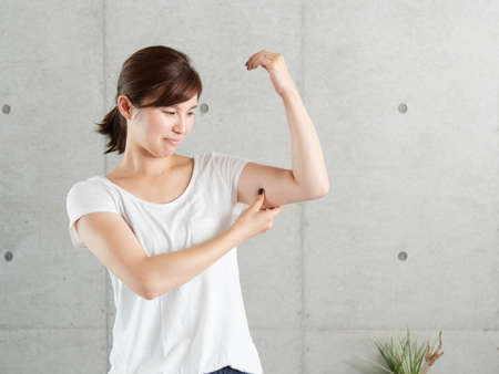 Photo for A Japanese woman who worries about the sagging of two arms - Royalty Free Image
