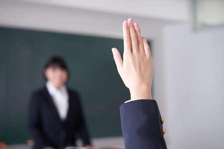Photo pour Japanese female junior high school student  raises  hand  in the classroom - image libre de droit
