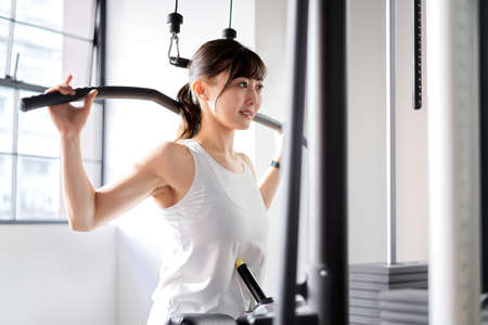 Photo for Asian woman back rat pull-down at training gym - Royalty Free Image
