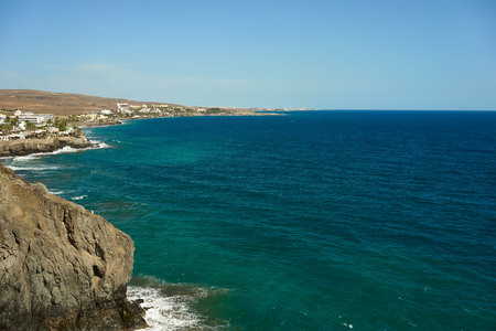 View down the cliffs of Gran Canaria on the wide Atlantic ocean green and blue water under great cliffs of Gran Canaria