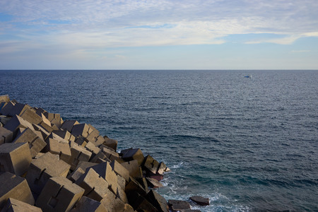 View on breakwater and on the wide Atlantic ocean of Gran Canaria green and blue water under great cliffs of Gran Canaria