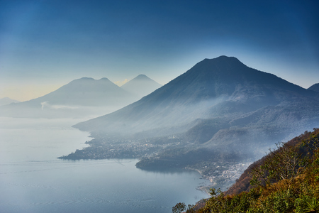 Foggy morning at lake in Guatemala in the morning hours / Highlands with volcanoes at Lake Atitlan in Guatemala / Famous tourist spot in Guatemala