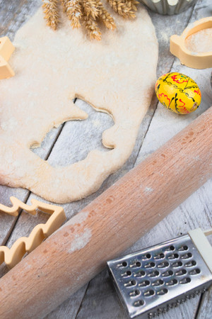 Photo pour Easter baking preparation. Raw dough and form for the holiday cookies on a wood table. - image libre de droit