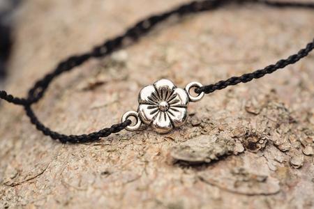 Tiny fashionable female bracelet on wooden background