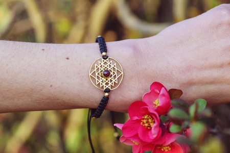 Photo pour sacred geometry metal natural stone bracelet on female wrist - image libre de droit