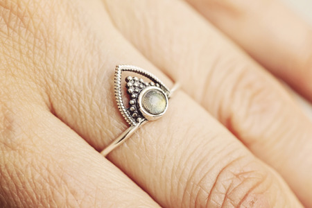 Photo pour Female hand wearing silver ring with labradorite gemstone - image libre de droit