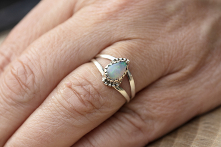 Photo pour Silver ring with opal gemstone caboshon on female hand - image libre de droit