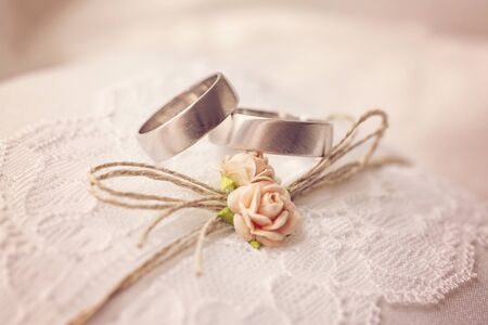 Foto für Wedding ring on lace pillow with sweet artificial small rose blossoms - Lizenzfreies Bild