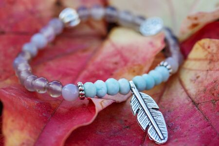Photo pour Metal feather pendant mineral stone bracelet on autumn background - image libre de droit