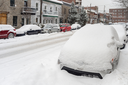 Montreal, CA - 12 December 2016: Cars covered in snow during snowstorm