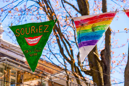 Montreal, CA - 13 May 2020: Souriez, Ca va bien aller (smile, Its going to be ok) message and rainbow drawing on pennants near Laurier Street.