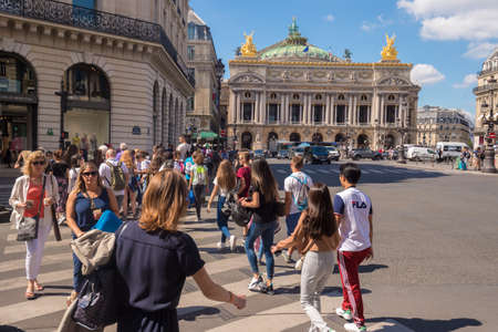 Paris, France - 25 June 2018: A crowd of people crossing Rue de la Paix near Paris Opera Garnier.
