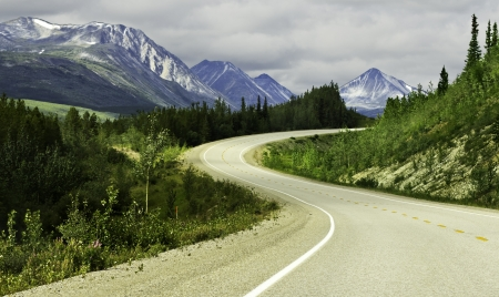 Curved asphalt road in high mountains of Alaska