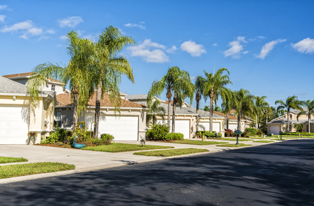 Photo pour Typical gated community houses with palms and asphalt road, South Florida - image libre de droit