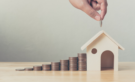 Photo pour Property investment and house mortgage financial concept, Hand putting money coin stack with wooden house - image libre de droit