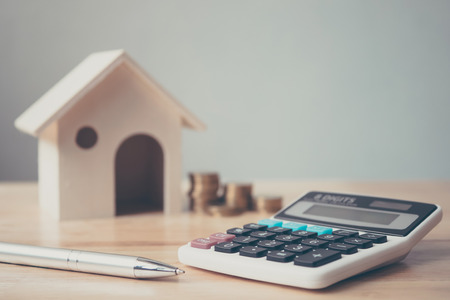 Photo for Calculator with wooden house and coins stack and pen on wood table. Property investment and house mortgage financial concept - Royalty Free Image