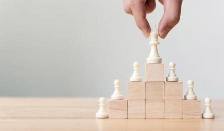 Foto de Business leadership concept with chess on top wood block ladder staircase. Team leading career for teamwork - Imagen libre de derechos