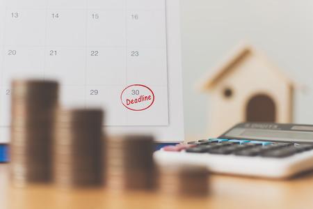 Foto de Tax payment season and finance debt collection deadline concept. Money coins stack, calendar, calculator and wooden house - Imagen libre de derechos
